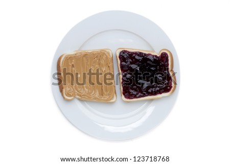 Close up image of peanut and strawberry jam sandwich on white plate