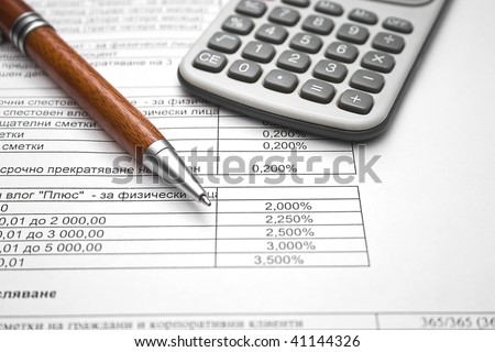 Close up image of pen and calculator on financial documentation