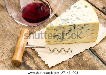 Close up image of piece of blue cheese with overturned wineglass and corkscrew on wood background - stock photo