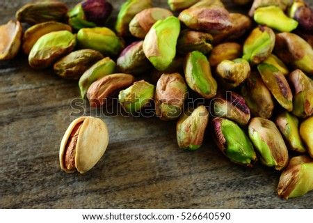 Close-up image of pistachios on wooden background