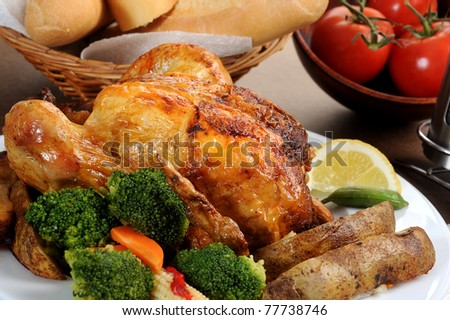 Close-up image of roasted chicken on a plate with veggies