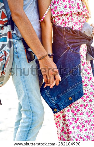 Close up image of romantic hipster sweet couple in love, holding hands, bright sunset colors, stylish outfits. - stock photo