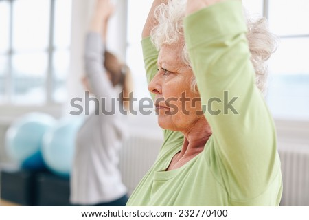 Close-up image of senior woman practicing yoga at gym. Active senior woman exercising at health club with female trainer in background. - stock photo