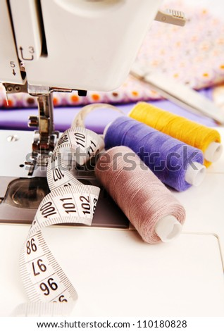 Close up image of sewing machine with colored threads and sartorial meter - stock photo