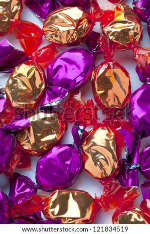 Close-up image of shiny golden and purple hard candies randomly arranged over white.