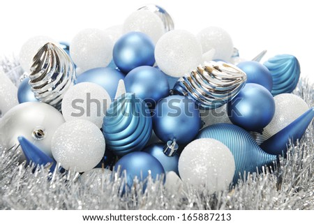 Close-up image of silver, white and blue Christmas bulbs on a bed a tinsel garland.  On a white background.