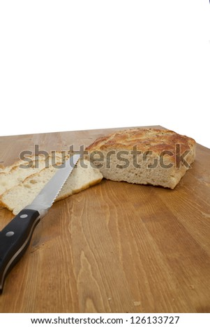 Close up image of sliced loaf with bread knife on wooden table