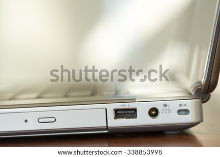 Close-up image of the side of a laptop showing part of DVD drive door and ports.  - stock photo