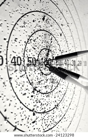 Close up image of three arrows hit the center of dartboard; In black and white - stock photo