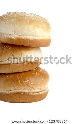 Close-up image of three burger buns covered by sesame seeds isolated on a white background