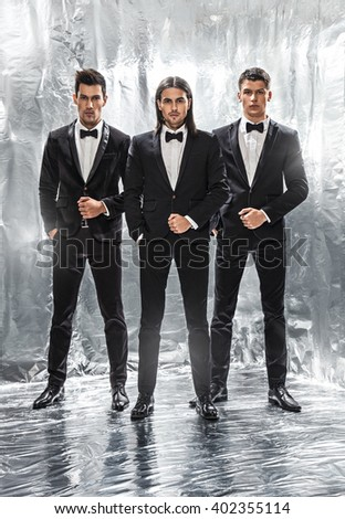 Close up image of three business men in black suit,silver background - stock photo