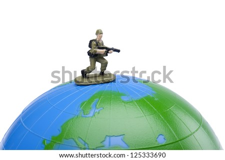 Close up image of toy soldier on the top of the globe protecting it - stock photo