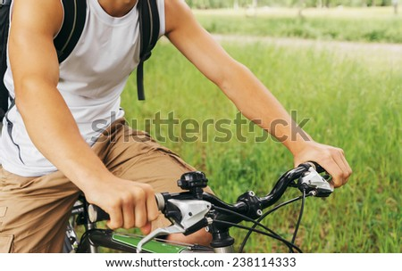 Close-up image of unrecognizable cyclist man's hands holding handlebar of mountain bike in summer park