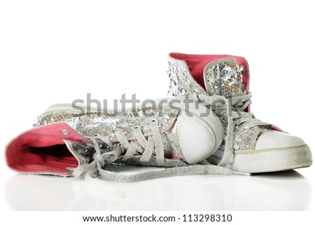 Close-up image of used girls' sparkly sneakers with bright pink linings.  On a white background. - stock photo