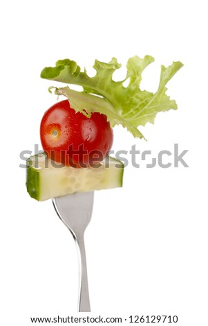 Close up image of vegetables salad on fork isolated on white background