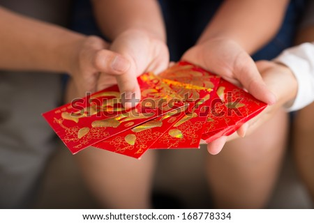 Close-up image of Vietnamese red envelopes with money being presented on Tet holiday on the foreground  - stock photo