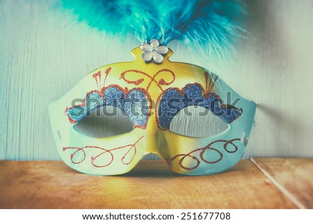 close up image of vintage Venetian masquerade mask on wooden table  - stock photo