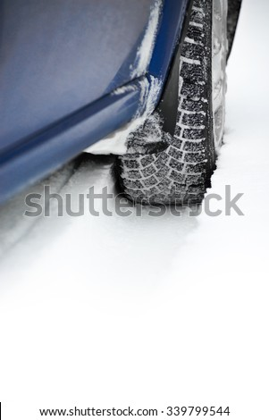 Close-up Image of Winter Car Tire on the Snowy Road. Drive Safe Concept - stock photo