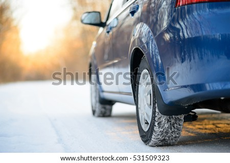 Close-up Image of Winter Car Tire on the Snowy Road. Drive Safe Concept.