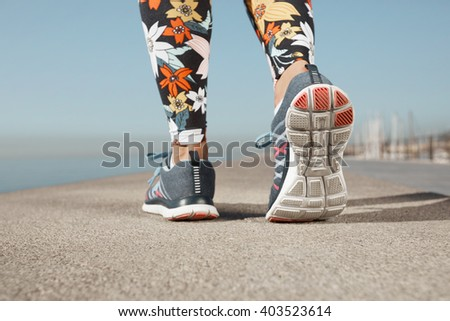 Close up image of woman's running shoes during outdoor training. Cropped portrait of a female athlete jogging on pavement on a sunny wearing floral sportswear. Girl working out outdoors in the city - stock photo