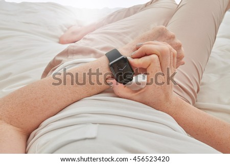 Close up image of woman using smartwatch to check time. Female lying on bed using smart wrist watch. - stock photo