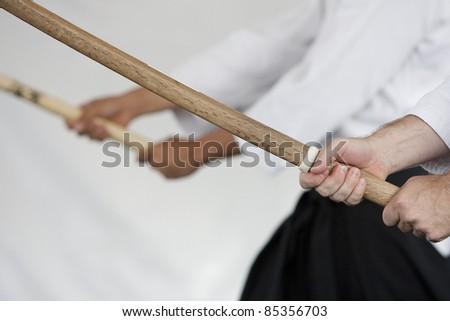 Close up image of wooden swords (bokken) held by Japanese swordmanship practitioners. - stock photo