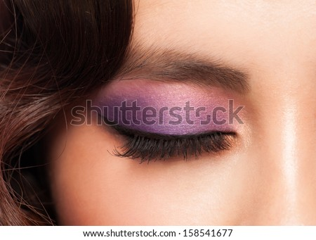 Close-up image of young asian woman eye with bright violet makeup