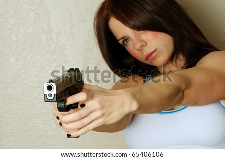 Close up image of young attractive female pointing gun at someone breaking and entering
