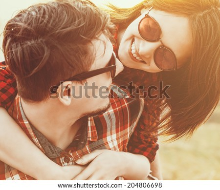 Close-up image of young happy woman embraces a man. Low contrast, with sunlight effect - stock photo