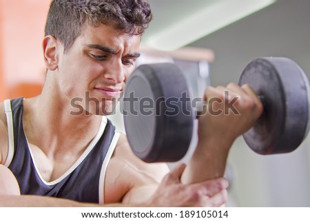 Close up image of young man lifting weights - stock photo