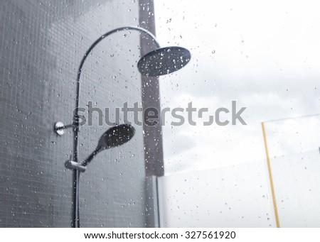 close-up image water drops splash on mirror, design of home interior of bathroom, shower head in bathroom - stock photo