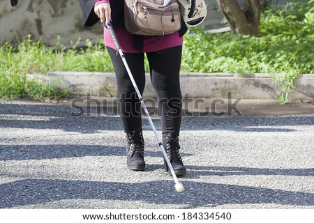 Close up in blind woman's feet with stick - stock photo