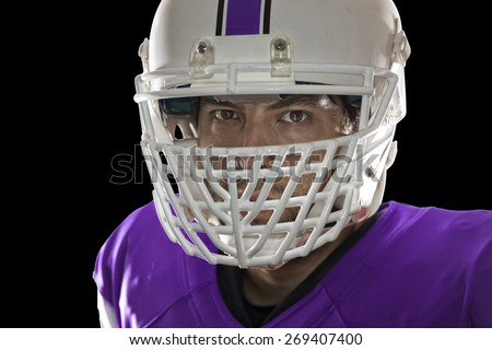 Close up in the eyes of a Football Player with a purple uniform on a black background.