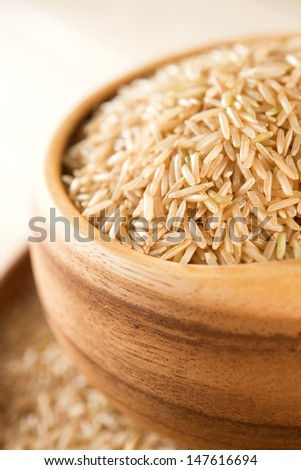 Close up India raw organic basmati brown rice in wooden bowl - stock photo