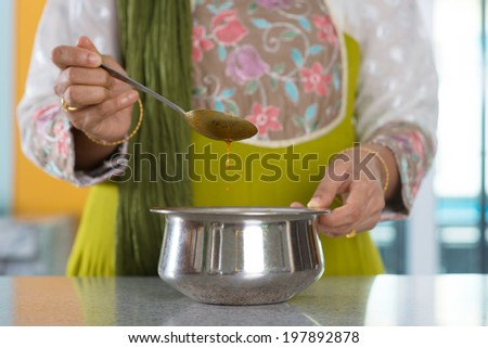 Close up ?Indian woman preparing meal, stirring curry sauce, focus on the bowl.