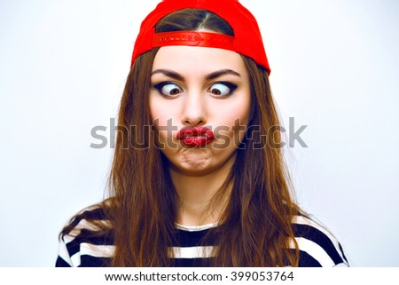 Close up indoor fashion lifestyle portrait of cool pretty young brunette girl, amazing long hairs, bright makeup, red hat and stripy t shirt, cute face, image with flash. making crazy funny grimace.
