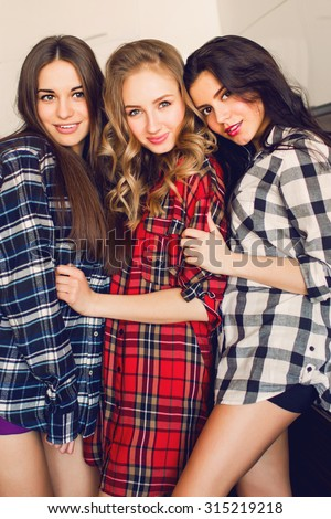 Close up indoor lifestyle portrait of three funny young friends posing  indoor . Home party mood. Wearing plaid shirt. Warm soft photo. - stock photo