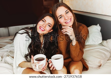 Close up indoor lifestyle portrait of two pretty cheerful   girls  holds  cup of coffee .   Sisters hugs and have great time together in the morning  time.  - stock photo