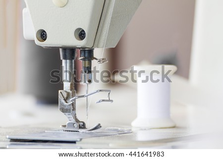 Close up industrial sewing machine in textile factory