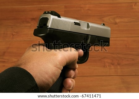 Close up isolated image of male holding pistol - stock photo
