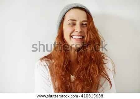 Close up isolated portrait of beautiful redhead girl wearing cap and white T-shirt, winking and smiling at the camera with happy and cheerful look, against gray concrete wall. Human face expressions - stock photo