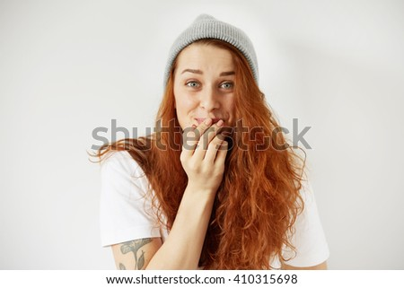 Close up isolated portrait of young redhead woman laughing, covering mouth with her hand with surprised and funny look. Human face expressions, emotions, body language. Film effect, selective focus - stock photo