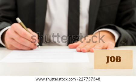 Close up Job Text on Small Wooden Piece in Front Businessman while Writing on White Table. A Simple Job Concept. - stock photo