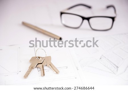 Close-up key on the plan of house, financial contract, pen and glasses. - stock photo