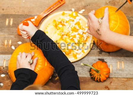 Close-up kids hands carving Halloween pumpkins