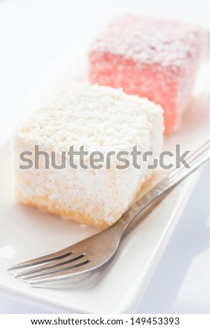 Close up lamington sponge cakes and fork, stock photo