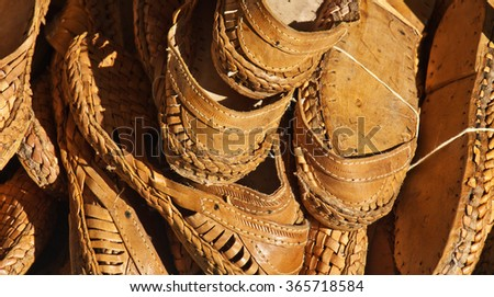 Close-up: large group of leather lightweight sandals. Openwork structure, braided inserts, decorative firmware, light-brown tones. Useful for background.