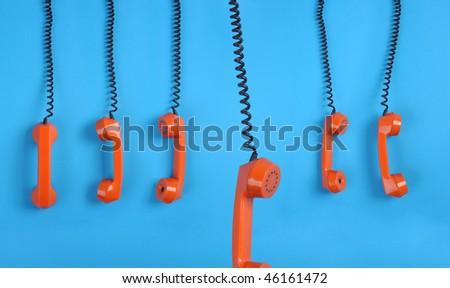 Close-up large group of orange telephones over blue background - stock photo
