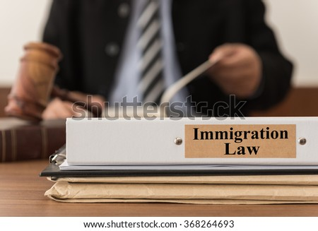 close up lawsuit folder of immigration law with the judge is considering a lawsuit in background. concept of immigration law.