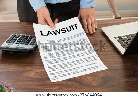 Close-up Lawyer Showing The Document With The Text Lawsuit - stock photo